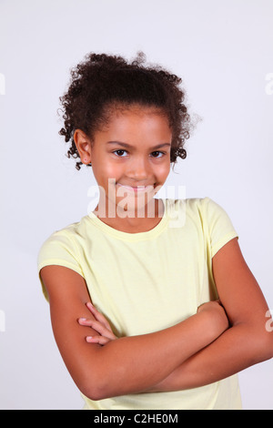 Studio portrait of a smiling African-American girl with arms folded - Stock Image