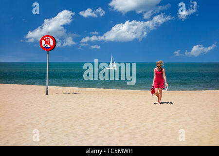 Young woman in red dress walking on sandy beach in no swimming zone along the Belgian North Sea coast in summer, Belgium - Stock Image