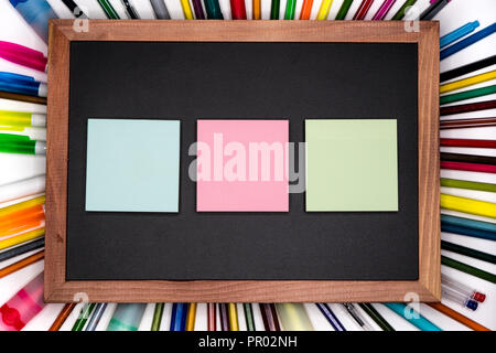 Colorful adhesive notes on blackboard with pencils on background, blank copy space - Stock Image