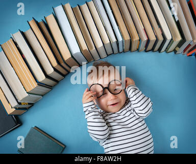 One year old baby with spectackles and books - Stock Image