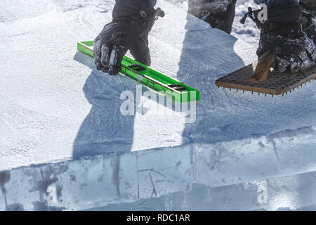 Ice sculptor using a level and nail board at the Lake Louise Ice Magic Festival in Banff National Park, Alberta Canada - Stock Image