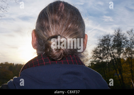Middle aged man with his hair  in a bun, from behind - Stock Image