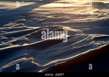 Strong winds blow across the surface of icy snow in the late setting sun creating an arctic freeze - Stock Image