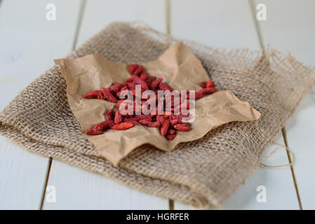 Goji Berries on white wooden background. Wolf berry - Stock Image