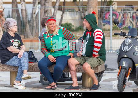 Benidorm, Costa Blanca, Spain, 25th December 2018. British tourists dress for the occasion on Christmas Day in this favourite getaway destination for Brits escaping the cold weather at home. Temperatures will be in the mid to high 20's Celsius today in this mediterranean hotspot. Couple on bench wearing Christmas jumpers and hats. - Stock Image