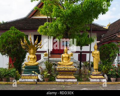 Gilded buddha in one of temples Luang Prabang Royal Palace and national museum is a set of buildings in French colonial style dating back to 1904 - Stock Image