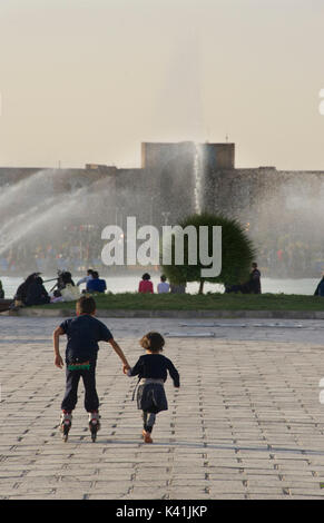 Iranian children rollerskating in Naqsh-e Jahan Square, known as Imam Square.  A popular square in the centre of Isfahan, Iran. Ali Qapu Palace right - Stock Image