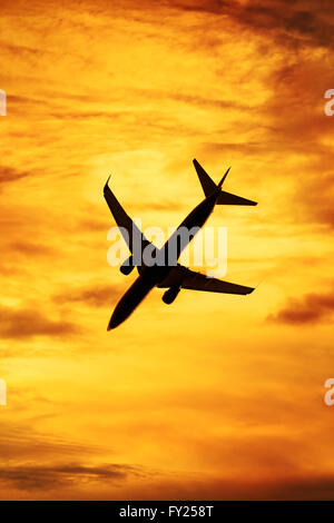 Sunset silhouette of passenger aircraft - Stock Image