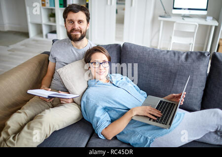 Restful young man and woman in casualwear lying on sofa and enjoying leisure at home - Stock Image