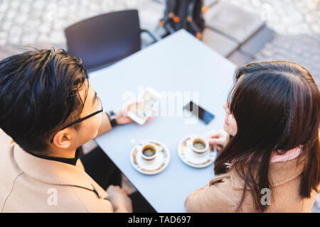 Young couple with cell phone in a street cafe - Stock Image