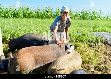 Hard working woman farmer on small farm doing chores of bringing water and feeding pigs outside Decorah, Iowa, USA - Stock Image