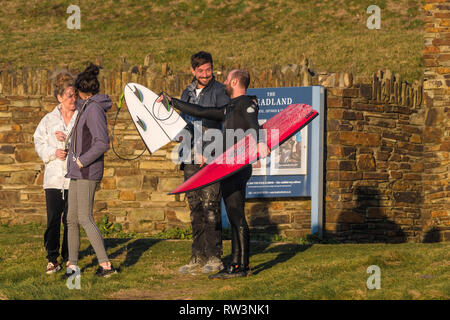 A surfer explaining to people how his surfboard snapped in the sea at North Fistral in Newquay Cornwall. - Stock Image