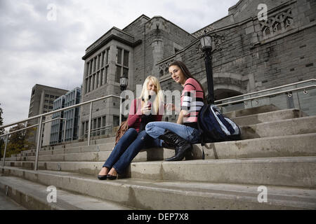 Portrait of two female college students sitting on the steps of a building, University of British Columbia, Vancouver, BC, - Stock Image