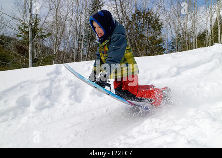 A little boy (6 yrs old) doing a jump on his sledge - Stock Image