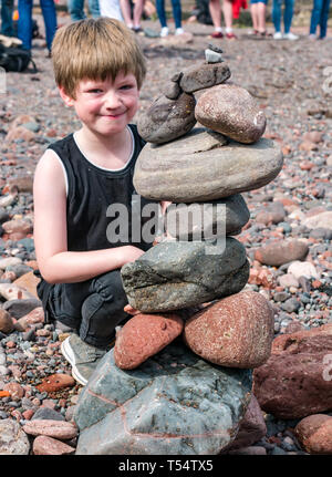 Dunbar, East Lothian, Scotland, UK. 21st Apr 2019. European stone stacking championship: Christian  balances stones in the Quantity competition for children under 15 years of age –- most stones balanced vertically - at Eye Cave beach on the second day which comprises 2 competitions, a 3 hour artistic challenge and a children's competition. The overall winner receives a trip to llano Earth Art Festival & World Stone Balancing competition in Texas in 2020. Credit: Sally Anderson/Alamy Live News - Stock Image