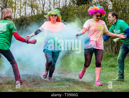 Two women with coloured wigs being covered in paint on Macmillan cancer charity 5K colour fun run. - Stock Image