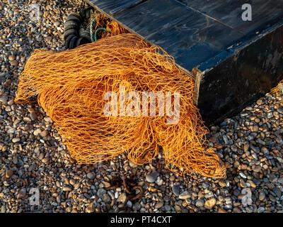 Nylon orange fishing net spilling from a black wooden box on a pebble beach - Stock Image
