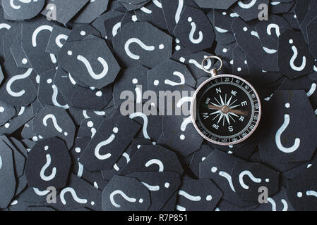 Compass with moving rod on question mark background. Concept of travel, navigation, explore and where to go - Stock Image