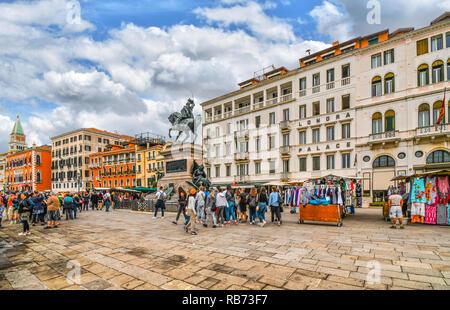 Tourists crowd the market stalls near the Vittorio Emanuele statue on the Riva degli Schiavoni promenade on the Grand Canal near St. Mark's Square - Stock Image