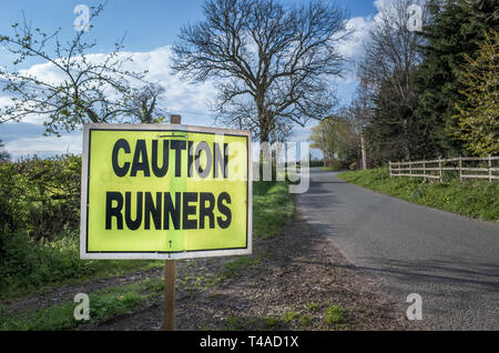 Caution sign warning of runners in an official race around the countryside. - Stock Image