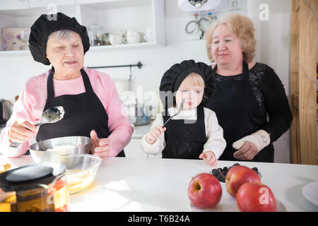 Happy family making pancake in the kitchen - Stock Image