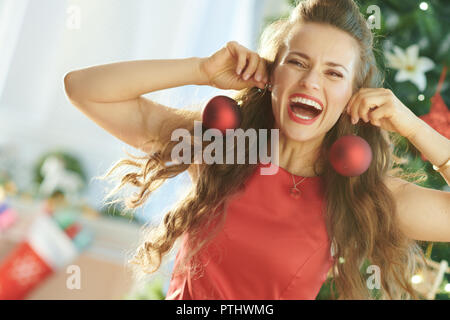 happy young woman in red dress near Christmas tree having fun time - Stock Image
