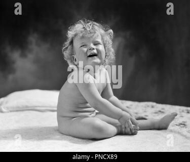 1930S LAUGHING NAKED CURLY HAIRED BABY LOOKING UP - b10034 HAR001 HARS MALES EXPRESSIONS B&W HAPPINESS CHEERFUL CURLY UP HAIRED SMILES JOYFUL BABY BOY GROWTH JUVENILES LOOKING UP BLACK AND WHITE CAUCASIAN ETHNICITY HAR001 NO CLOTHES OLD FASHIONED SITTING UP - Stock Image