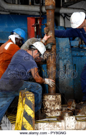 Workers holding rusty pipe on offshore oil platform - Stock Image
