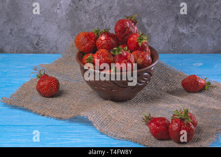 Ripe juicy strawberries in a clay bowl - Stock Image