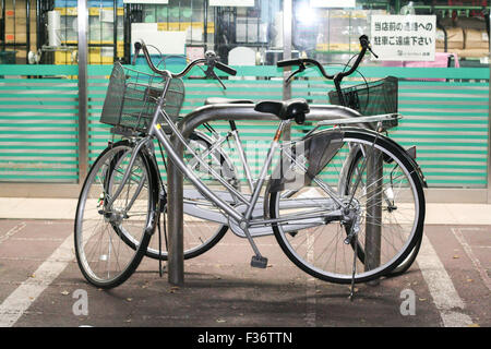two silver bicycles bike mamachari parked - Stock Image
