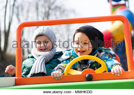 Two happy boys sitting in a wooden spring car on a playground of the Cytadela park in Poznan, Poland - Stock Image