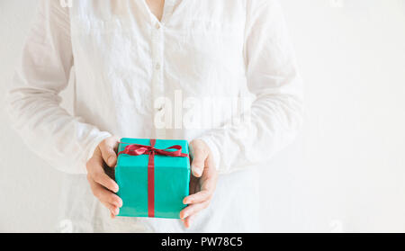 Young caucasian woman holds in hands gift box wrapped in green paper tied with red ribbon. White background pastel colors. Christmas New Years Valenti - Stock Image
