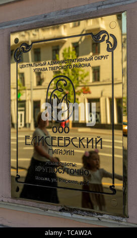 Woman and girl reflected in the brass plaque of the famed Eliseevsky Gastronom #1 food store at Tverskaya 14, Moscow Russia - Stock Image