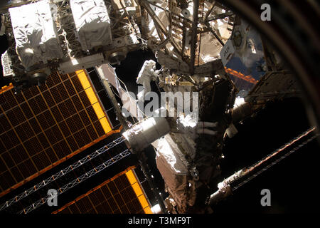 Expedition 59 David Saint-Jacques of the Canadian Space Agency and NASA astronaut Anne McClain (red stripes on spacesuit) work upgrading the power supply during a spacewalk outside the International Space Station April 8, 2019 in Earth Orbit. Astronauts McClain and Hague spent six-hours and 30-minutes outside the space station to upgrade the power supply for the Canadian-built robotic arm, known as Canadarm2, and installed cables to provide for more expansive wireless communications coverage outside the orbital complex. - Stock Image