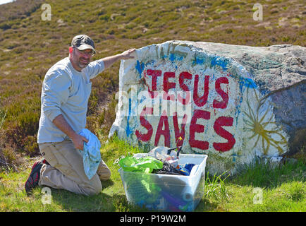 The Rev Rich Moller refreshes the famous Jesus Stone on Dava Moor near Grantown on Spey in Morayshire after the stone had been vandalised. - Stock Image