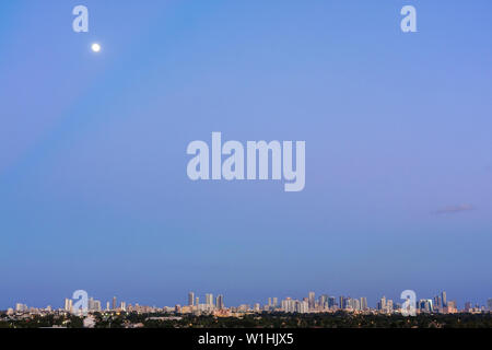 Miami Florida downtown skyline buildings moon dusk panoramic - Stock Image