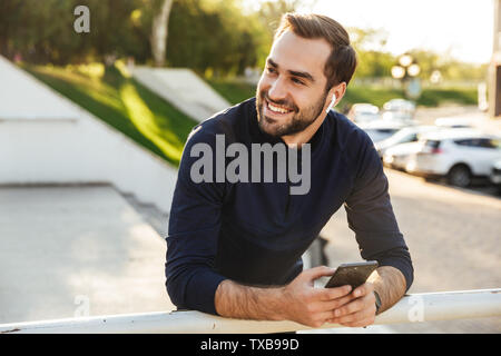 Image of a handsome happy young strong sports man posing outdoors at the nature park location using mobile phone listening music with earphones. - Stock Image