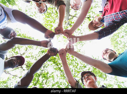 View from below mens group joining fists in circle, hiking under trees - Stock Image