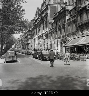 1950s, tree lined side road next to the Avenue des Champs-Elysees, Paris, France, with cars of the era parked outside the cafes and shops that line this famous Parisian landmark. - Stock Image
