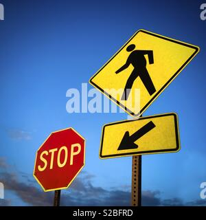 Pedestrian crossing walk sign  pointing to an stop signage - Stock Image