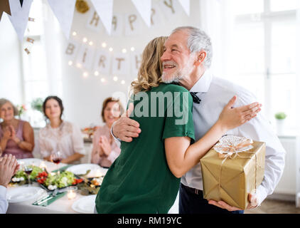 Young woman giving a gift to her grandfather on indoor party, hugging. - Stock Image