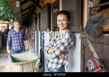 Portrait of woman farmer standing near horse at stable outdoor - Stock Image