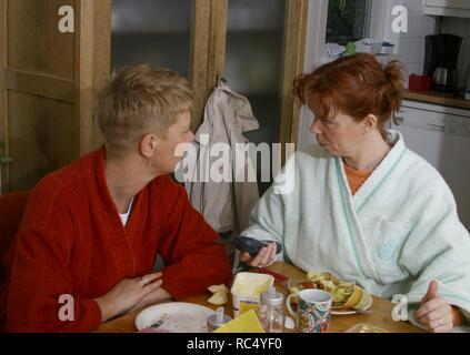 Two adult women sit at table in housecoat and discuss or argue at home. - Stock Image