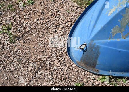 Upturned front of a blue fiberglass rowing boat with natural sunlight and stone background - Stock Image