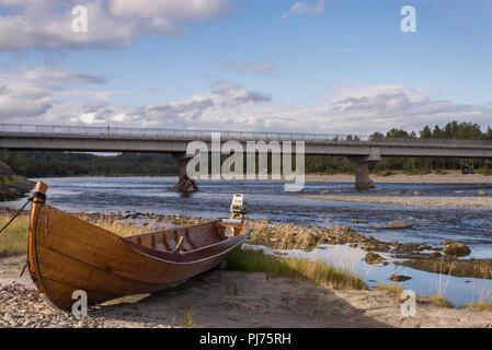 Øvre Alta bridge, river boat at river shore. - Stock Image
