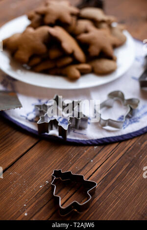 Cookie cutters by plate of Christmas cookies - Stock Image