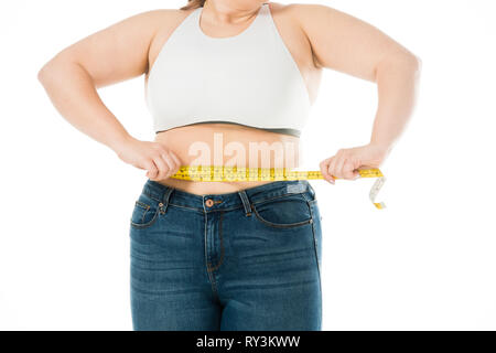 cropped view of overweight woman measuring waist isolated on white - Stock Image