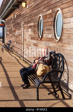 Senior man sleeping in the sunshine on Southend Pier. - Stock Image