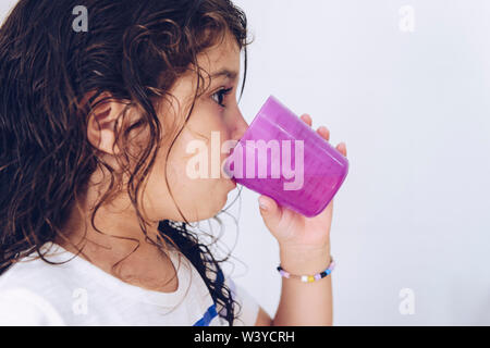 portrait of a little girl rinsing her mouth after brushing teeth in the bathroom before going to bed after taking a shower, kids hygiene concept, copy - Stock Image