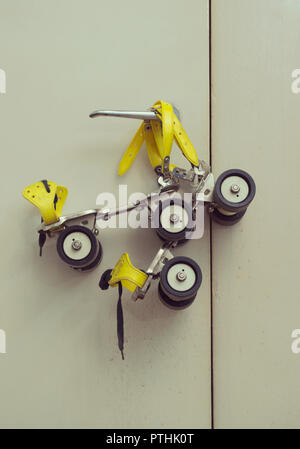 1970s old roller skates hanging on door handle - Stock Image